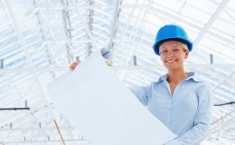 Happy lady architect holding blueprint at construction site